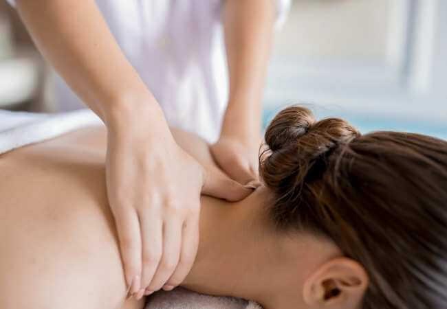 Mujer acostada boca abajo mientras recibe un masaje en la nuca, cuello y hombros para aliviar el dolor de los nervios y columna.