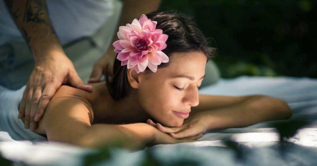 Mujer acostada boca abajo en una camilla recibiendo un masaje en los hombros.