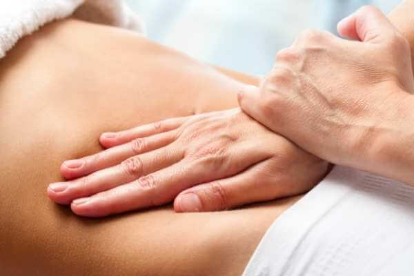 Terapeuta realizando presiones y movilizaciones con la palma de su mano sobre el vientre de su clienta, a modo de drenar y reequilibrar el sistema digestivo