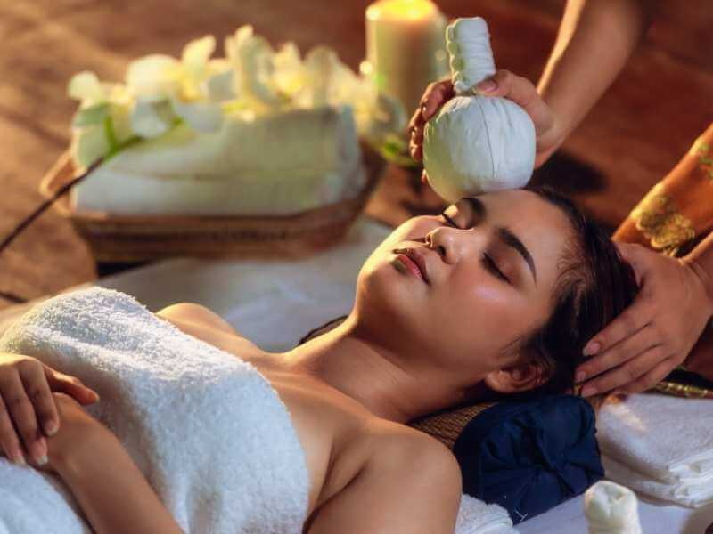 Joven mujer recibiendo un masaje para el dolor de cabeza que aplica pindas herbales calientes como método curativo.