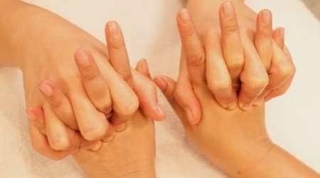 Terapeuta realizando jalones y empujes suaves para descontracturar las articulaciones de los dedos de las manos de una clienta-