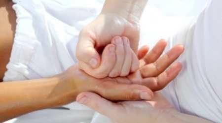 Masajista presionando los nudillos de su puño cerrado en la palma de una clienta como parte de un masaje en las palmas de las manos.