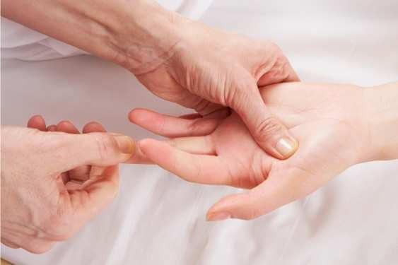 Terapeuta halando levemente de la punto de un dedo para relajar las articulaciones y hacer presiones de reflexología durante un masaje en las manos.
